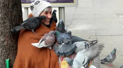 Old homeless woman sitting on a street surrounded by pigeons smiling and begg Stock Footage