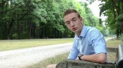 Handsome man sits in a park and talks to camera Stock Footage