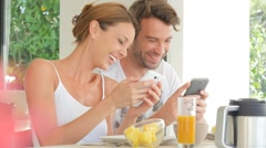 Couple having fun using smartphone at breakfast time Stock Footage