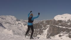 Women runs to the top of a mountain and punches the air. Stock Footage
