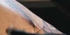 Close-up of tattoo being drawn on a woman's back - stock footage