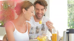 Cheerful couple eating pineapple for breakfast Stock Footage