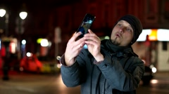 The guy on the street at night makes a funny Selfe by the phone Stock Footage