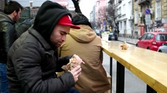 The guy in a bully and a thug in a red cap and hood have a burger on the str - stock footage