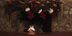 Three stocking full of gifts hanging from a fireplace mantel - stock footage