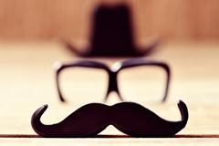 mustache, eyeglasses and hat forming the face of a man - stock photo