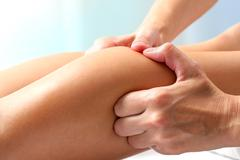 Athlete having therapeutic calf muscle massage. Stock Photos