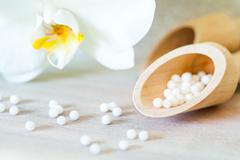 Homeopathic pills with orchid. Stock Photos