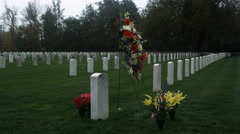 Floral tributes among rows of grave markers in a veterans' cemetery Stock Footage