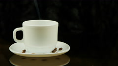 A cup of hot coffee on a black background Stock Footage