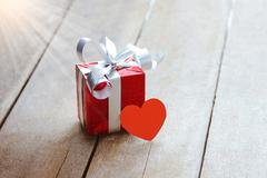 Red gift box and heart on white wooden table - stock photo