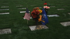 Stock Video Footage of A mourner kneels and brushes away leaves from a veteran's gravestone