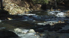 Rapids on a partially frozen rocky stream Stock Footage