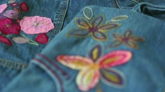 Structure of denim decorated with needlework, fabric applique. Denim background Stock Footage