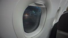Airplane passenger looking through plane window at airport. Night flight delay Stock Footage