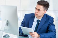 Businessman synchronizing digital tablet with computer. - stock photo