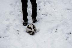 child's legs and soccer ball on snow background - stock photo