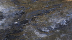 Close-up of a narrow stream flowing between chunks of ice Stock Footage