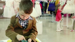 Boy with a smartphone. Waiting in the store Stock Footage