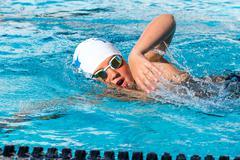 Close up action shot of teen swimmer. Kuvituskuvat