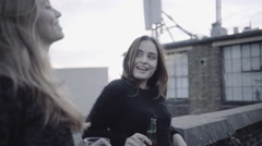 Young adult women talking and drinking on rooftop party Stock Footage