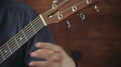 close up male tuning the acoustic guitar slow motion - stock footage