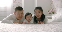 Young Asian family with a 6 month child on the bed looking at the camera Stock Footage