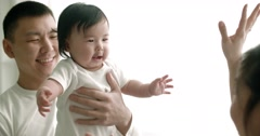 Young Asian family playing with 6 month old baby, slow motion Stock Footage