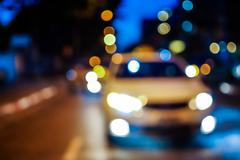 Blurred night street with car and lights bokeh - stock photo