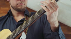 close up man taking chords on acoustic guitar slow motion - stock footage
