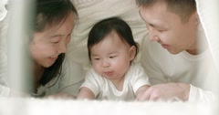 Young Asian family with a 6 month child on the bed Stock Footage