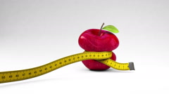 Measuring tape wrapped around a apple Stock Footage