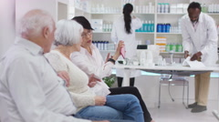 4K Bored customers waiting for medication at the pharmacy check the time Stock Footage