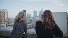 Young adult women looking out on rooftop Stock Footage
