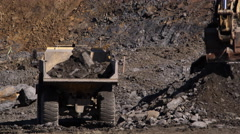 Dumptruck receiving a bucketfull of rock at an excavation site Stock Footage