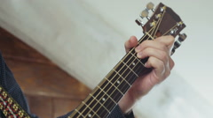 close up mans hand taking chords on acoustic guitar slow motion - stock footage