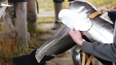 Man putting on armour plates before knights tournament at outdoor history museum Stock Footage