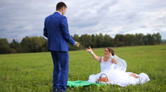 Bride and groom on a green meadow in summer day - stock footage