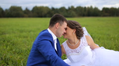 Bride and groom on a green meadow in summer day Stock Footage