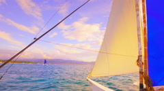 Yacht boat with white and blue sails floating on sea at sunset to Boracay island Stock Footage
