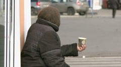An elderly woman begging on the street. - stock footage