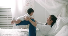 Young Asian mother with her 6 month old baby, slow motion Stock Footage