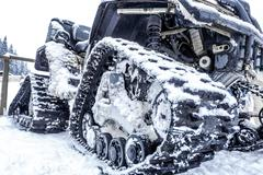 Closeup of a caterpillar snowmobile with snow - stock photo