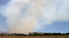 Smoke from a wildfire blowing toward threatened homes in Palmdale, California - stock footage