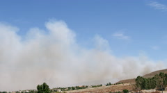 Heavy smoke blows toward houses in the path of a wildfire - stock footage
