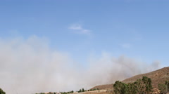 Firefighting plane flies past smoke from a wildfire - stock footage