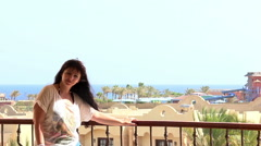 Woman on a balcony overlooking the sea in Egypt, having fun Stock Footage