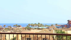 Woman on a balcony overlooking the sea in Egypt Stock Footage