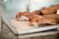 Stock Photo of Masculine hands typing on laptop keyboard