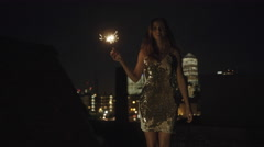 Young adult woman dancing on rooftop with sparkler Arkistovideo